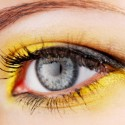 Beauty. Woman eye with yellow eyeshadow.